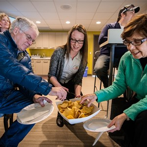 Patrons enjoy snacking on some nachos in a suite